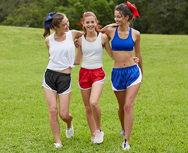 three young women walking across a field wearing soffe cheerleading shorts