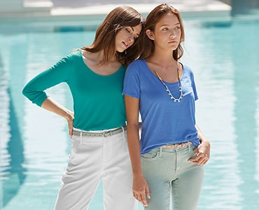 two women standing close together wearing delta platinum tee shirts in blues and greens